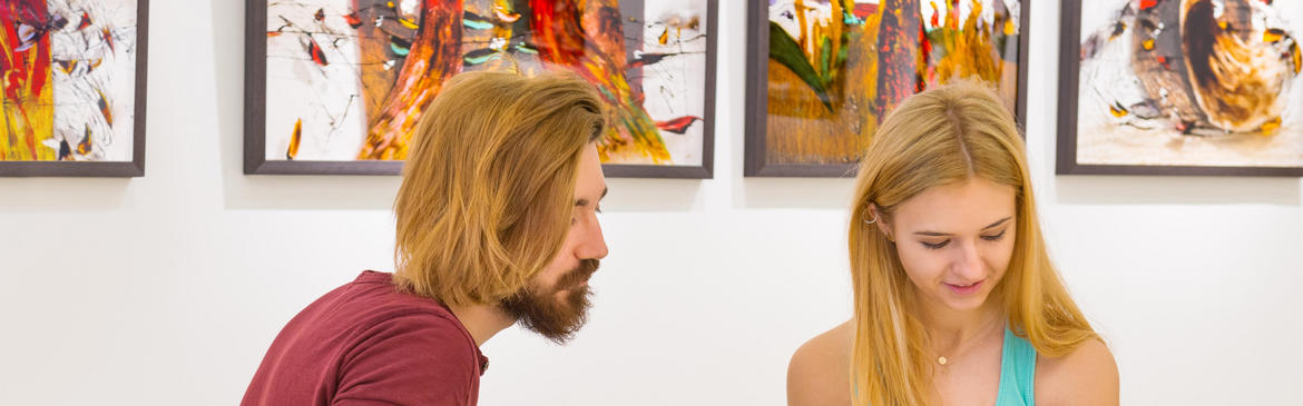 couple sitting in front of prints at a gallery