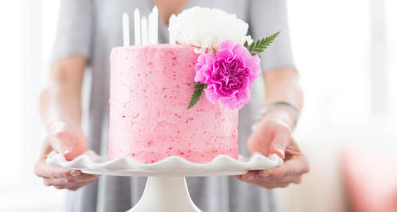 woman holding out pink cake on a cake plate