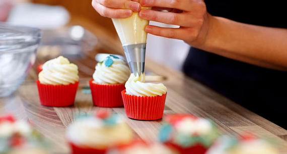 person using a piping bag to frost cupcakes
