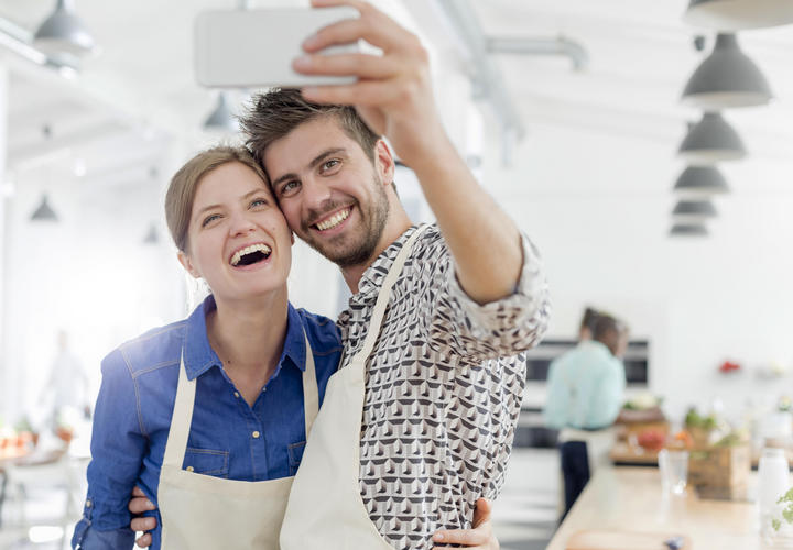 woman taking a picture of three people in cooking class