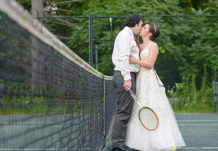newlywed couple kissing on a tennis court