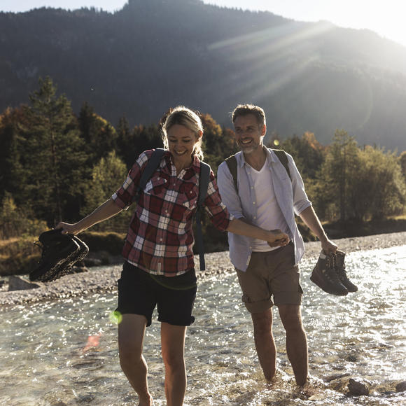 man and woman walking in riverbed